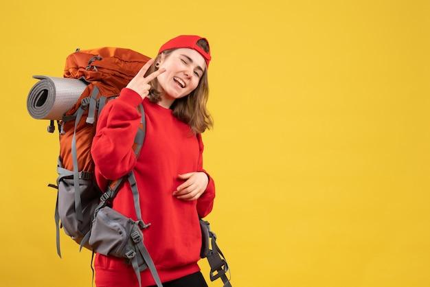 勝利のサインを身振りで示す赤いバックパックの正面図若い旅行者の女性