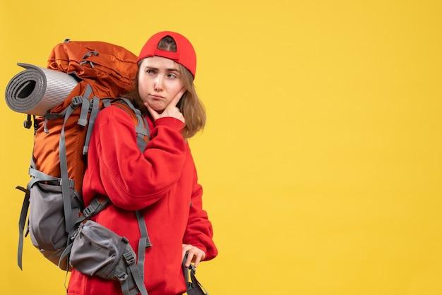 Donna giovane viaggiatore vista frontale in zaino rosso mettendo la mano sul mento