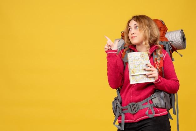 Vista frontale della giovane ragazza in viaggio in mascherina medica raccogliendo i suoi bagagli e tenendo la mappa che punta guardando indietro