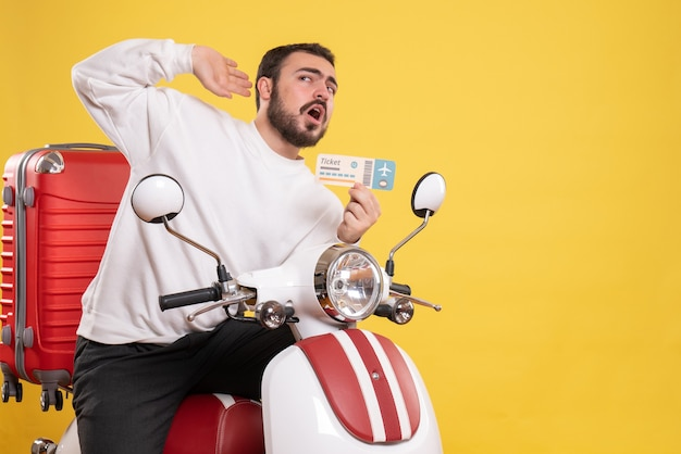 Front view of young travelling man sitting on motorcycle with suitcase on it holding ticket listening to the last gossiping on isolated yellow background