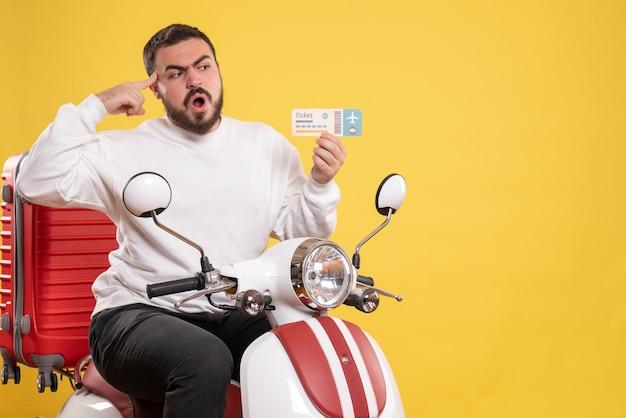 Vista frontale di un giovane uomo in viaggio incerto e incerto seduto su una moto con la valigia sopra che tiene il biglietto su sfondo giallo isolato