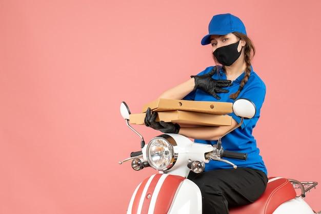 Vista frontale del giovane corriere femminile incerto che indossa maschera medica e guanti seduto su uno scooter che consegna ordini su sfondo pesca pastello