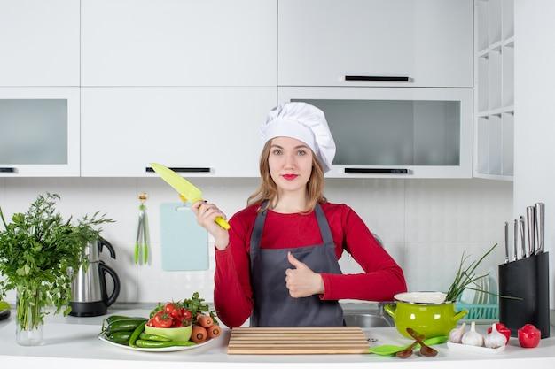 Giovane donna di vista frontale in grembiule che sostiene il coltello che fa i pollici sul segno