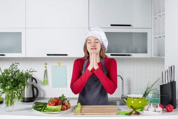 Front view young woman in apron joining hands together and wishing something