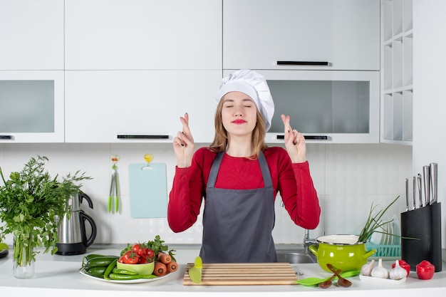 Front view young woman in apron making good luck sign