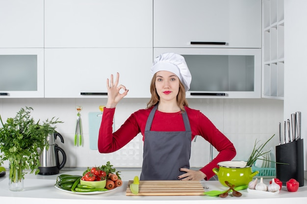 Front view young woman in apron making okey sign