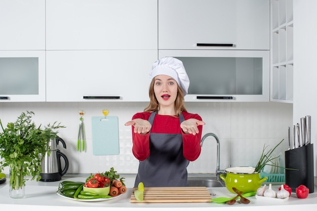 Front view young woman in apron opening her hands