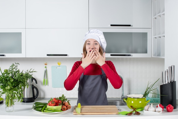 Front view young woman in apron putting hands on her mouth
