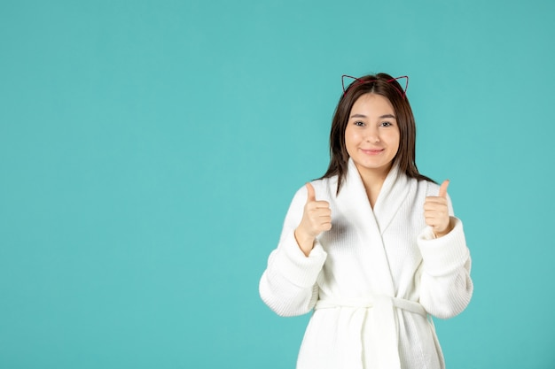 Front view of young woman in bathrobe on blue wall