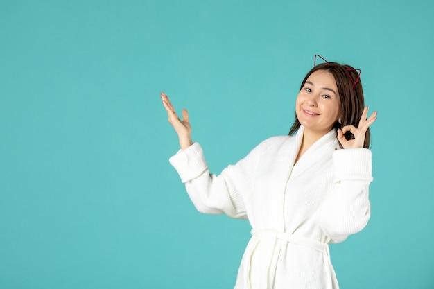 Vista frontale della giovane donna in accappatoio sulla parete blu