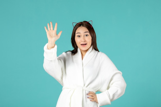 Front view of young woman in bathrobe waving on blue wall