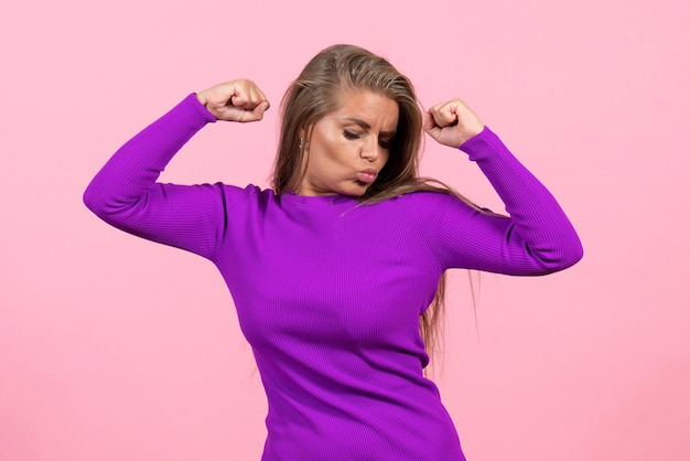 Front view of young woman in beautiful purple dress posing flexing on pink wall