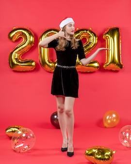 Vista frontale giovane donna in abito nero che mi fa firmare palloncini sul rosso
