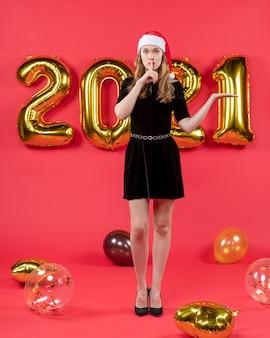 Vista frontale giovane donna in abito nero che fa segno shh palloncini su red