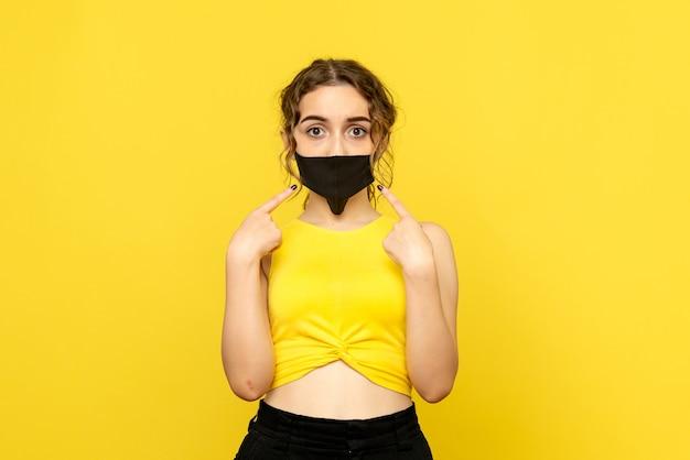 Vista frontale della giovane donna in maschera nera sulla parete gialla