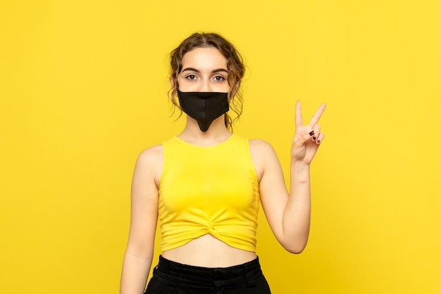 Front view of young woman in black mask on yellow wall