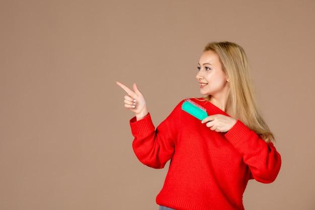 茶色の壁に彼女の髪を磨く正面図若い女性