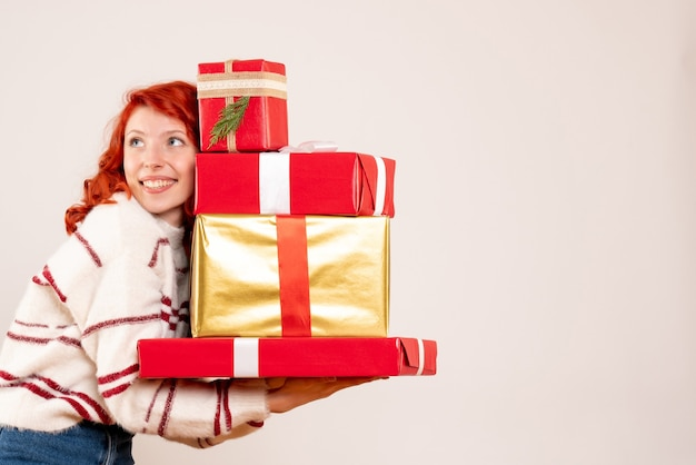 Front view of young woman carrying christmas presents on a white wall