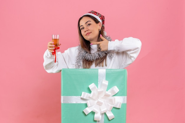 Front view of young woman celebrating christmas with drink on pink wall