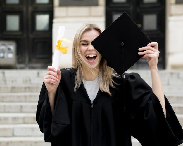 Вид спереди молодая женщина празднует свой выпускной
