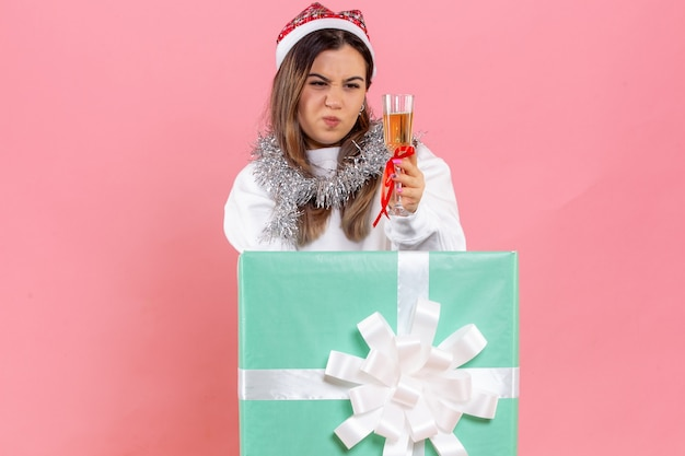 Giovane donna di vista frontale che celebra il natale con la bevanda su fondo rosa-chiaro