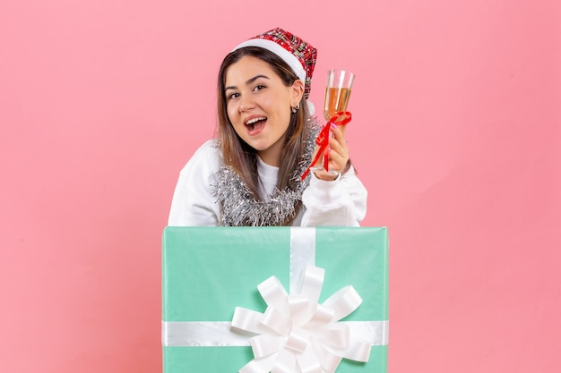 Front view of young woman celebrating xmas with drink on a pink wall
