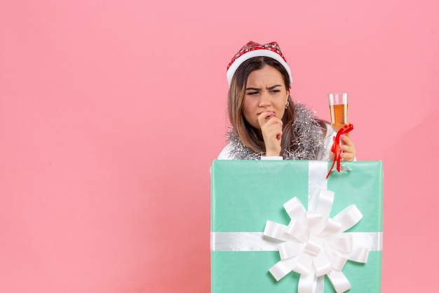 Front view of young woman celebrating xmas with drink on pink wall