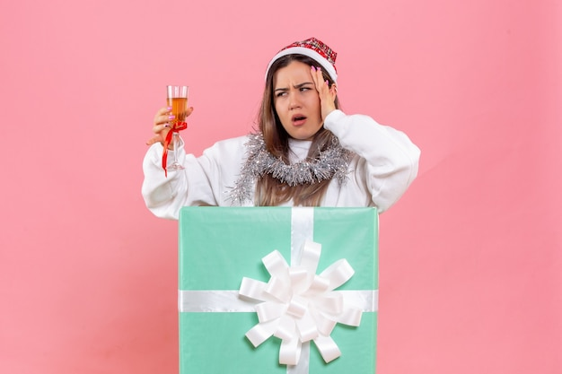 Front view of young woman celebrating xmas with drink on the pink wall