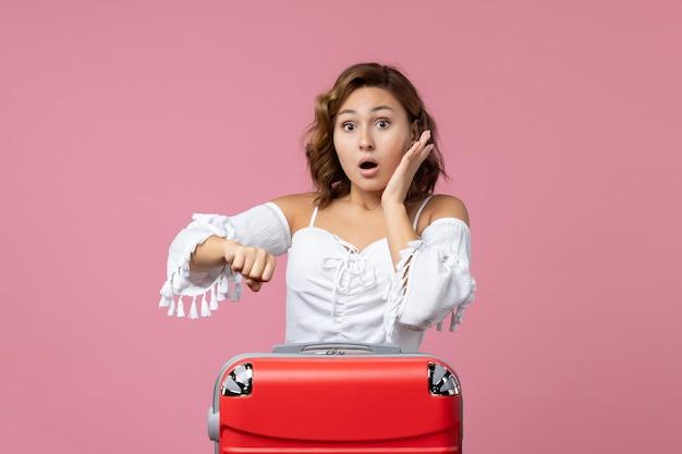 Vista frontale della giovane donna che controlla il tempo con la borsa da vacanza rossa sulla parete rosa