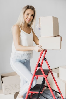 Front view young woman climbing ladder