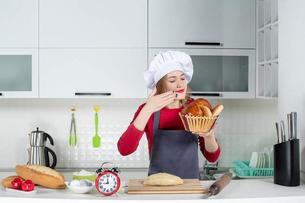 Front view young woman closing eyes in cook hat and apron smelling loaf in the kitchen