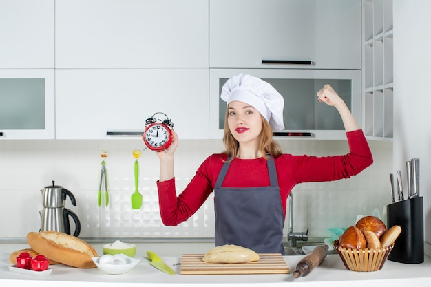 Front view young woman in cook hat and apron holding red alarm clock showing her arm muscle in the kitchen