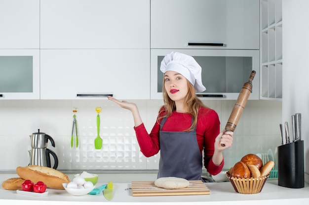 Front view young woman in cook hat and apron holding rolling pin in the kitchen