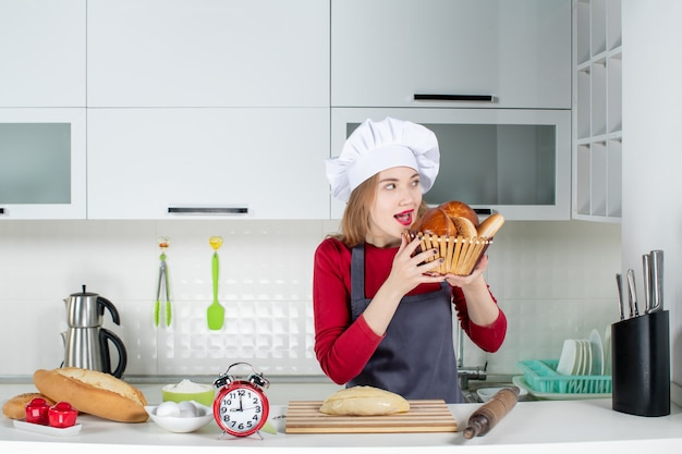 Front view young woman in cook hat and apron holding up loaf in basket in the kitchen