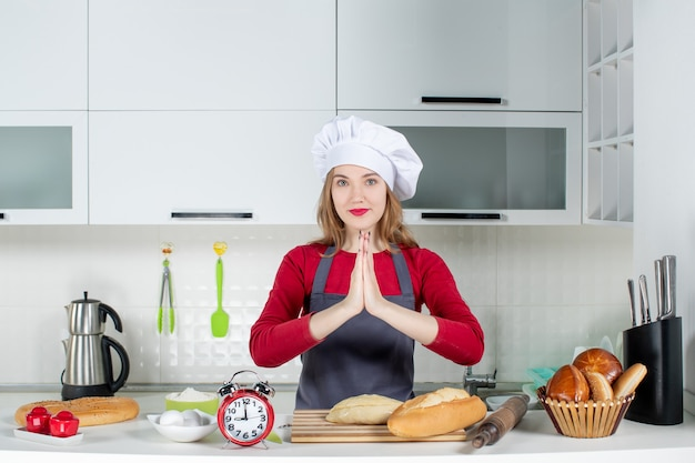 Front view young woman in cook hat and apron joining hands together in the kitchen