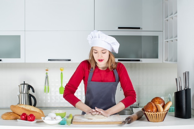 Front view young woman in cook hat and apron kneading dough in the kitchen