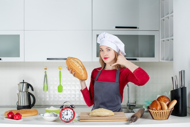Front view young woman in cook hat and apron making okey sign holding bread in the kitchen