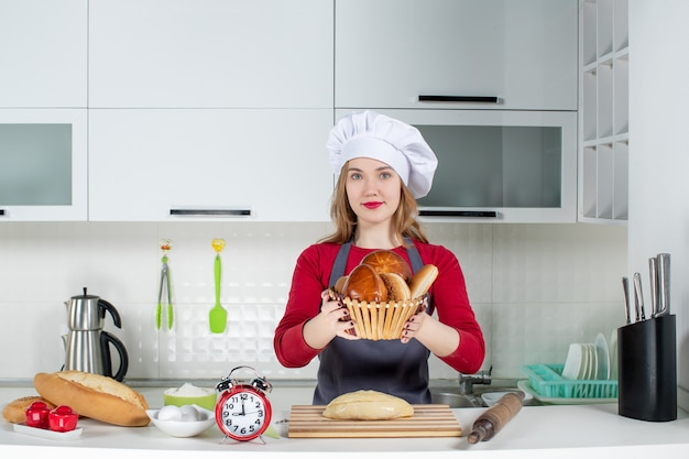 Front view young woman in cook hat and apron olding up basket with loaf in the kitchen