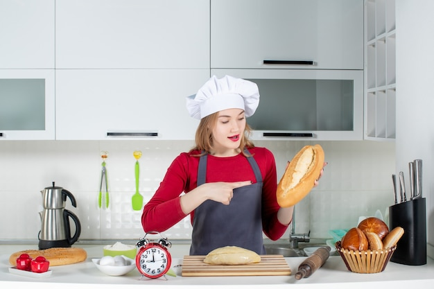 Front view young woman in cook hat and apron pointing at bread in the kitchen