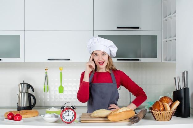 Vista frontale giovane donna con cappello da cuoco e grembiule che si mette la mano sulla vita in cucina