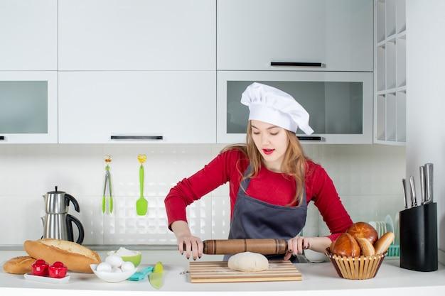 Vista frontale giovane donna con cappello da cuoco e grembiule che arrotola la pasta in cucina