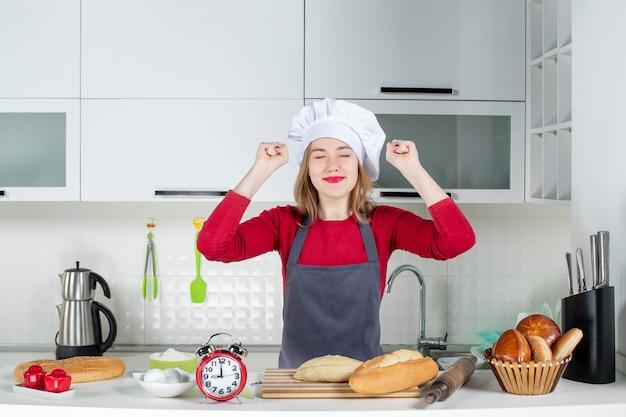 Vista frontale giovane donna con cappello da cuoco e grembiule che mostra la sua felicità in cucina