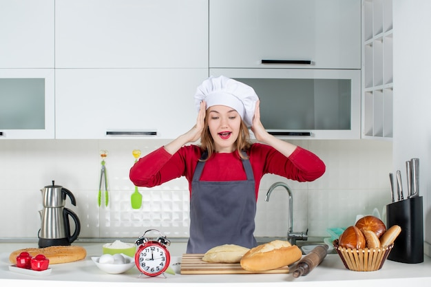 Front view young woman in cook hat and apron showing her surprise in the kitchen