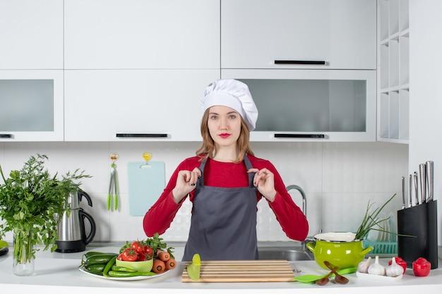 Giovane donna di vista frontale in cappello del cuoco che tiene il suo grembiule