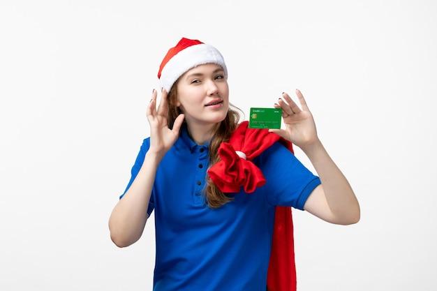 Vista frontale del corriere della giovane donna che tiene la carta di credito sulla parete bianca