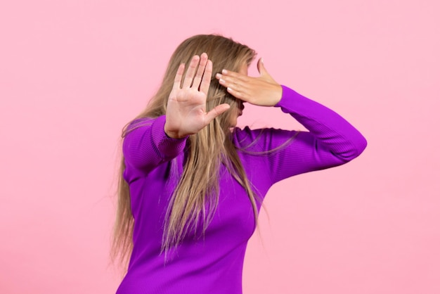 Front view of young woman covering her face in beautiful purple dress on pink wall