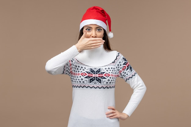 Giovane donna di vista frontale che copre la bocca sullo spazio marrone