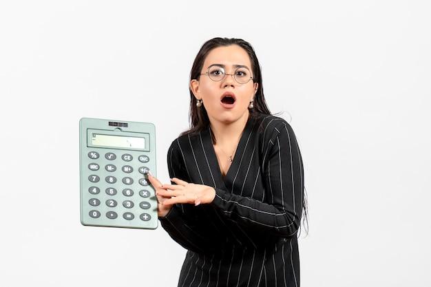 Vista frontale giovane donna in abito scuro rigoroso che tiene grande calcolatrice su uno sfondo bianco chiaro lavoro donna signora lavoratrice di moda bellezza