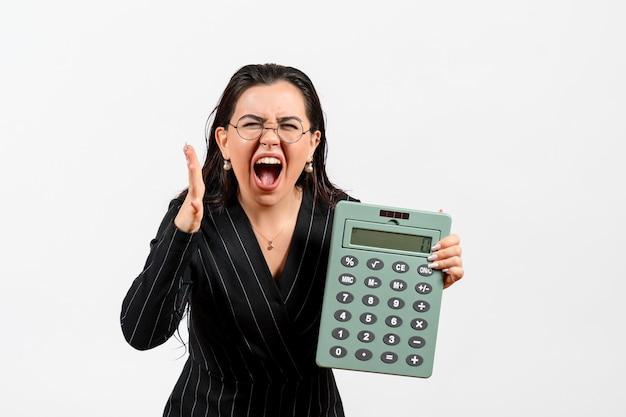 Vista frontale giovane donna in abito scuro rigoroso che tiene grande calcolatrice urlando su sfondo bianco lavoro bellezza donna moda ufficio affari