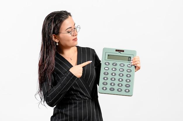 Vista frontale giovane donna in abito scuro rigoroso che tiene grande calcolatrice su sfondo bianco bellezza donna moda business lavoro d'ufficio